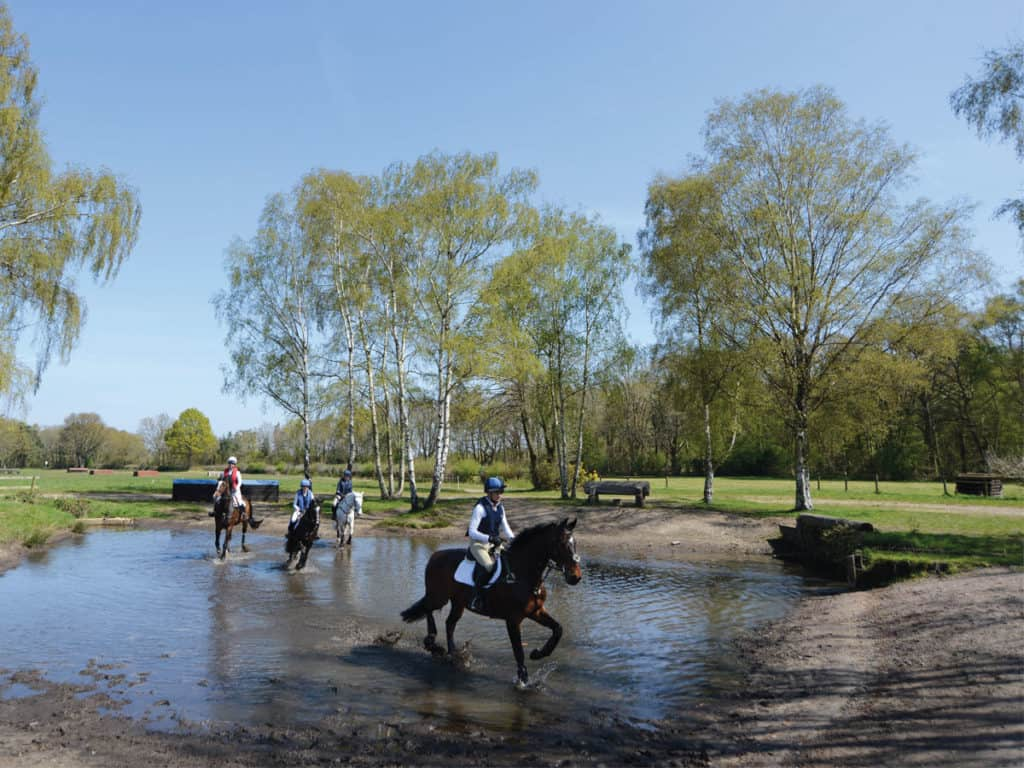 A group riding through a water jump