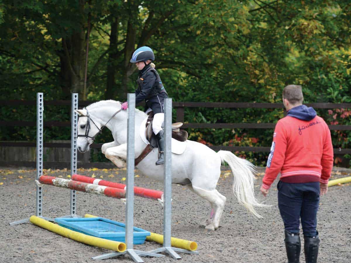 Robert Whitaker coaching a young rider jumping