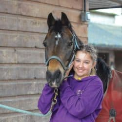 Girl cuddling her pony