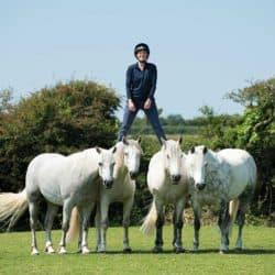 Emma Massingale standing on her pony' backs