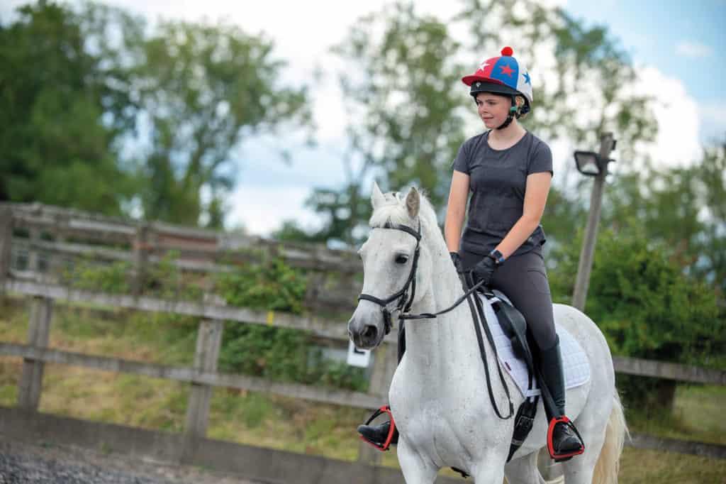 Girl riding grey horse